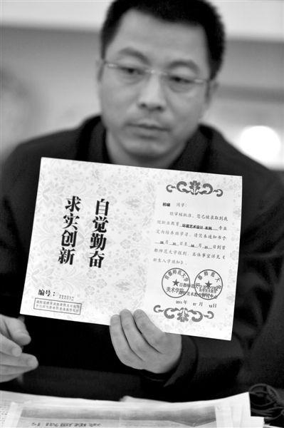 """昨日,首师大美术学院党委书记出示被骗学生的录取通知书,表示""""本科""""字样是由招生公司虚假宣传、擅自添加。新京报记者 浦峰 摄"""