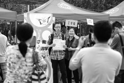 家长和学生在报名完成后,在学院迎新台前合影留念。京华时报记者潘之望摄