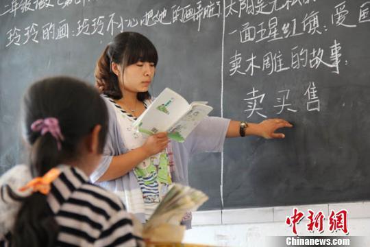 黑板一分为二,武家台小学乡村教师武淑洁给二、三年级的学生同时上课。. 闫慧 摄