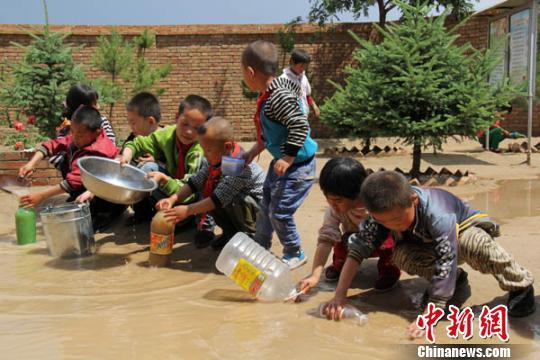 """一场大雨突如其来,武家台小学的孩子们在收集雨水,武淑洁说:""""这些雨水都收集到后面的窖里,过滤之后就可用了,之前一直吃着窖里的水。"""". 闫慧 摄"""