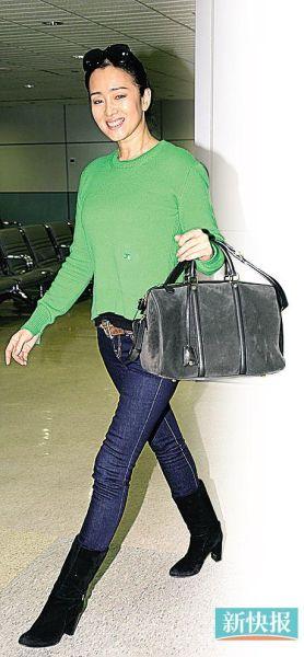 穿着绿色毛衣配牛仔裤的巩俐前日离开台湾时心情很好,全程笑容满面。