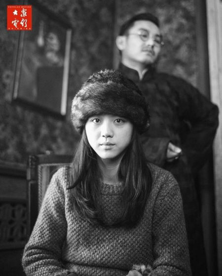 汤唯扮演的萧红表情肃穆,背后是袁文康扮演的萧红未婚夫汪恩甲