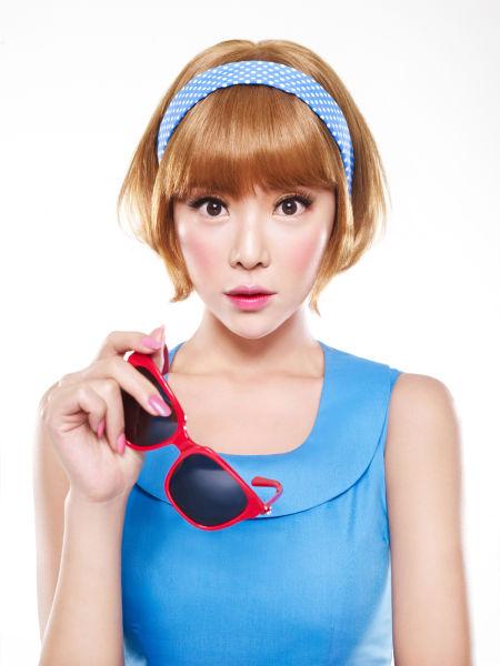 时尚的黄色短发头戴蓝色发卡,芭比娃娃般的可爱妆容甜美动人,尽展新颖