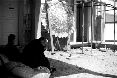 死者的哥哥嫂子坐在高虎家门前,低头抹泪。本报记者王苡萱摄