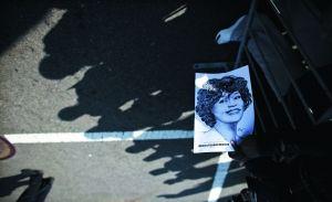 惠特尼的粉丝手拿印有她画像的海报,在街上向一代天后作最后的致敬。新华社 发