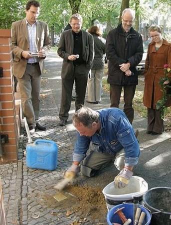 """昆特・德姆尼西在柏林的街道上铺设""""绊脚石"""" Photo by Axel Mauruszat 2008"""