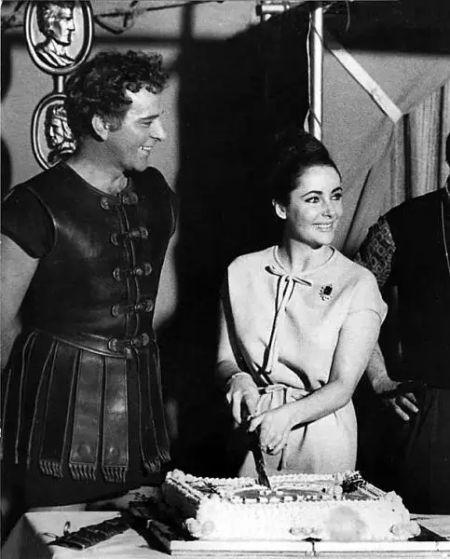 """伊丽莎白-泰勒在片场渡过生日时,理查德-伯顿还扮演成""""安东尼""""逗她开心。"""