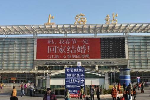 """在人头攒动的上海火车站大厅,一面巨大的广告屏上反复播着""""妈,我春节"""
