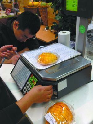 营业员在水果下加上一叠纸增加重量提高售价