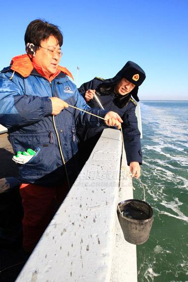 参加冰调任务的有关工作人员在B23测量点,正在对海水温度进行取样测量