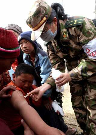 4月17日,公安边防部队医疗救护队医务人员在为受伤人员擦拭伤口消毒。