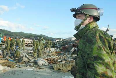 资料图:2011年3月27日,日本气仙沼,日本自卫队士兵在废墟中搜寻遇难者遗体。