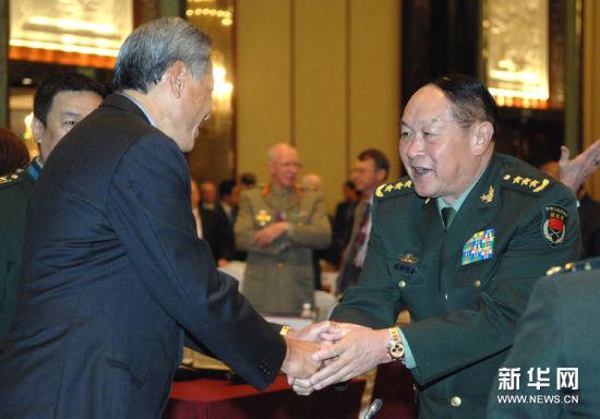 6月4日,中国国务委员兼国防部部长梁光烈(右)和新加坡国防部长黄永宏(左)在新加坡出席香格里拉对话会第二天的会议时握手。新华社发(邓智炜摄)