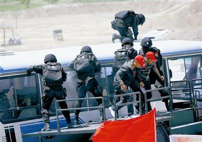 """今年5月,中国和吉尔吉斯斯坦、塔吉克斯坦在中国新疆喀什举行了""""天山-2号(2011)""""上海合作组织成员国执法安全机关联合反恐演习。图为特警队员冲入""""恐怖分子""""劫持的客车展开攻击。新华社发"""