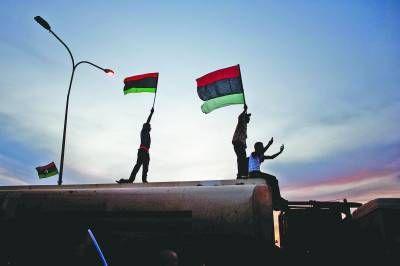 """22日,利比亚东部城市班加西举行仪式,欢迎从苏尔特前线归来的执政当局武装人员。几名青年站在卡车上挥舞""""过渡委""""的旗帜。新华社记者 韩冲摄"""
