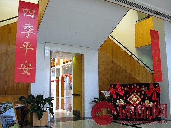 """在这个美军即将入驻的城市,议会大厦一进门处悬挂着""""出入平安""""的字幅,字幅下的展板贴满庆祝中国春节的红包、龙和福字,在迎接美国的同时迎接中国。"""
