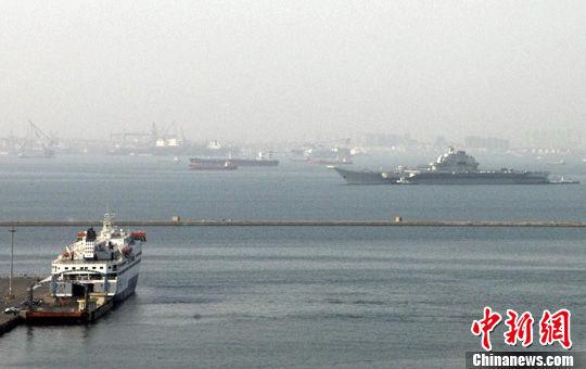 5月15日17时许,中国航母平台在完成为期9天的第六次海试后,驶回辽宁省大连港泊位。图为远眺中返航的航母平台。中新社发 董永君 摄