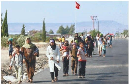 叙利亚危机已致大批难民涌入周边国家。图为22日叙利亚难民走出位于土叙边境的难民营。