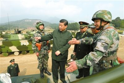 12月10日,习近平在广州军区某部训练场,登上两栖突击车了解装备情况。新华社发
