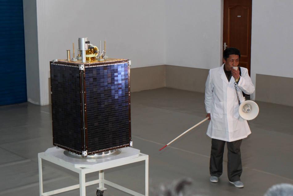 """4月8日,工作人员在位于朝鲜平安北道铁山郡东昌里的西海卫星发射场综合指挥所内现场展示即将发射的""""光明星3号""""地球观测卫星。"""