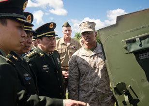 美军士兵为梁光烈讲解AAV7两栖战车性能