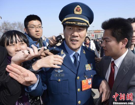 """3月3日下午,全国政协十二届一次会议在北京人民大会堂隆重开幕。朱德之孙朱和平委员入场前被记者追问""""钓鱼岛""""、航母等热点问题。中新社发 侯宇 摄"""