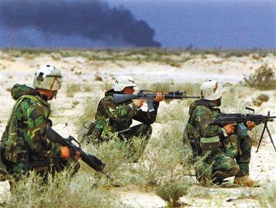 2003年3月21日,伊拉克战争爆发第二天,美国海军陆战队队员身后的油田冒出黑烟。