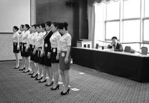 考场上,应试者一字排开统一站姿,以便考官观察体形■本报记者 王野 摄