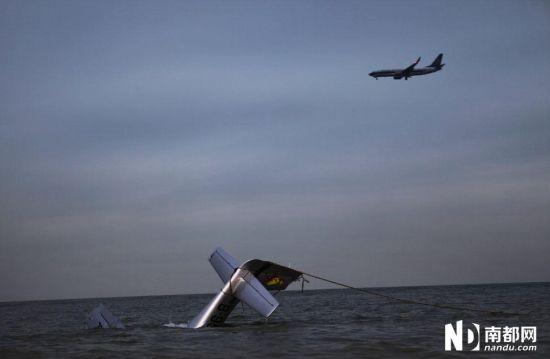 昨天,一架飞机从坠海的飞机上空飞过,坠海轻型飞机已经被救援队用绳索固定。南都记者 陈坤荣 摄