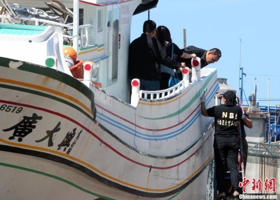 图为菲律宾国家调查局(NBI)人员手持放大镜,对船身弹孔进行鉴识。中新社发 刘舒凌 摄