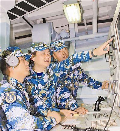 梁阳(左二)和官兵一起研究航模拖靶飞行轨迹。侯瑞摄
