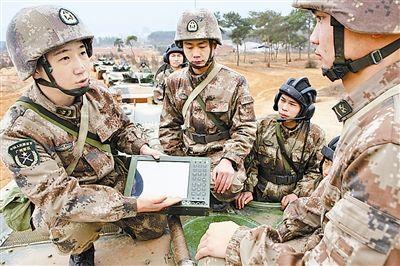 演练途中,杨铭(左一)给战友讲解车载计算机维护知识。(a href=