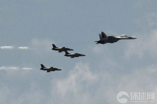 一架俄罗斯苏-30战斗轰炸机带领3架中国生产的K-8教练机组成编队飞过