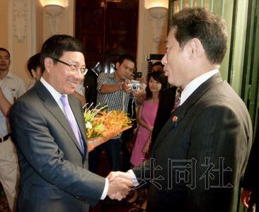 日本外相岸田文雄8月1日在河内同越南副总理兼外长范平明(左)握手