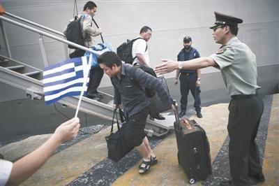 资料图:中国公民搭乘希腊军舰撤离利比亚后,于2日抵达雅典附近的比雷埃夫斯港,中方使馆工作人员在现场为其提供帮助。