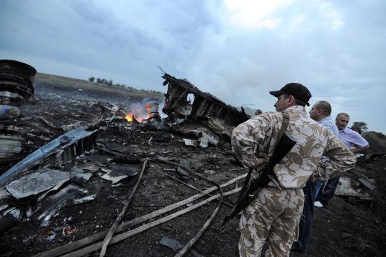 资料图:马航MH17客机被导弹击落现场,亲俄武装人员在检查坠机残骸。