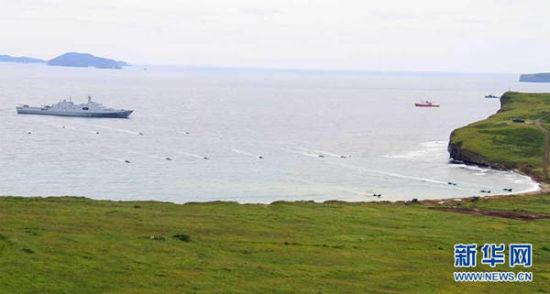 图为14辆两栖装甲从长白山舰庞大的登陆舱内鱼贯而出,划开浪花向滩头冲击