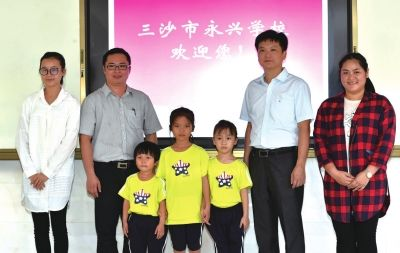 12日,永兴学校的小学老师江乔木(左一)、符贻梁(左二)、云小雯(右一)、副校长林春光(右二)和几名学生合影。
