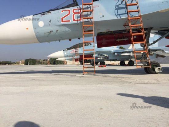 """2015年10月19日,俄罗斯国防部公开称,俄军仍在叙利亚执行打击IS极端武装任务,主要空袭IS的基础设施。当天,驻叙利亚""""Hmeymim""""空军基地的俄空军战机起飞了55架次打击近60个目标。图为""""Hmeymim""""基地内挂空空导弹待命的苏-30SM战机。"""
