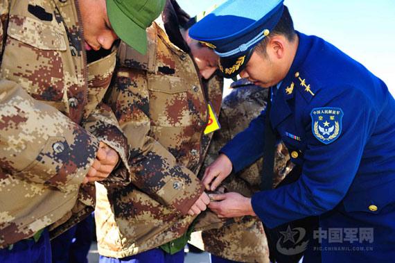 部队及时为刚下飞机的新兵发放07式防寒大衣。