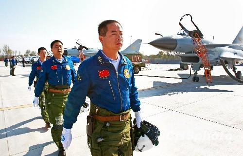 10月31日,八一飞行表演队所在师师长严锋(前一)带领歼10表演飞行员走向飞机准备训练。中新社发谭超摄
