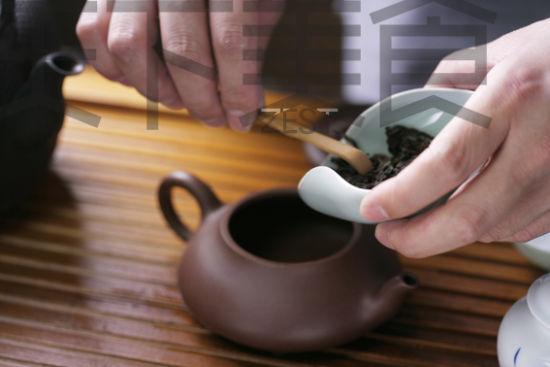 用茶匙将散茶荷里的散茶叶拨进茶壶