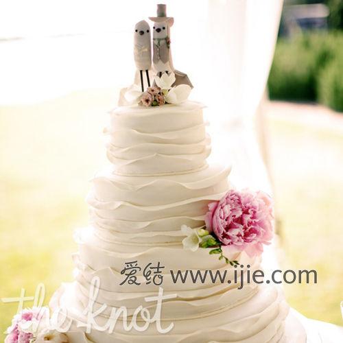 蛋糕的造型是仿新娘婚纱的层叠设计,顶端的两个小人也很可爱哦~!