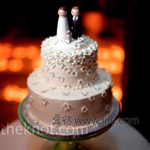 婚礼蛋糕是两层的小巧可爱的款式,上面还有两个传统的小人偶.