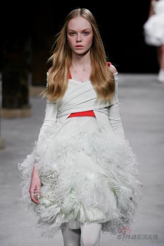这种轻盈的羽毛与同样轻盈的纱搭配,使圆形裙也显得飘逸而轻盈