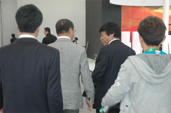 范伟在吉奥领导的携手护送下走出车展