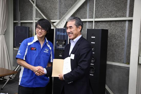 韩寒代表斯巴鲁中国拉力车队和斯巴鲁总社的日月本部长互赠礼物