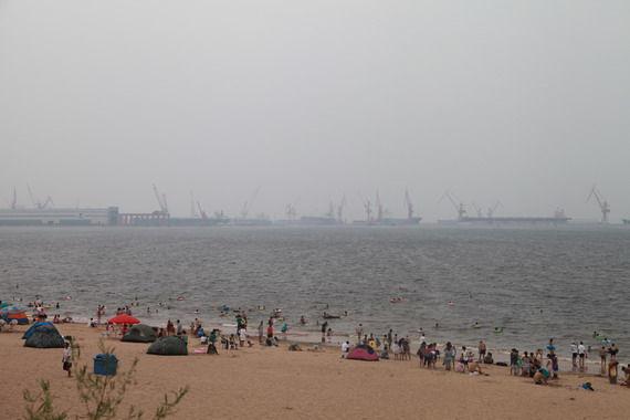 老龙头的沙滩上有不少游客,远处是修船厂