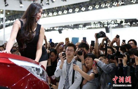 4月26日,2014年北京国际车展迎来公众日首个周末,不少参观者手持各式拍照设备拍摄车模。中新社发 韩海丹 摄