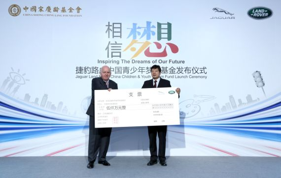 捷豹路虎大中华区总裁高博(左一)向中国宋庆龄基金会常务副主席齐鸣秋(右一)捐赠人民币5000万元支票